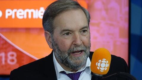 Thomas Mulcair derrière un micro dans un studio radio de Radio-Canada.