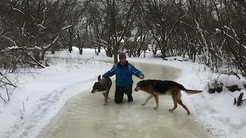 Un homme sur la glace avec deux chiens