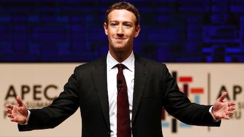Mark Zuckerberg en complet-cravate en train d'ouvrir les bras en direction d'une foule hors-cadre.