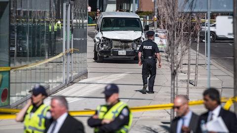 Des policiers discutent près de l'endroit où un camion a fauché plusieurs piétons, à Toronto, le 23 avril 2018.