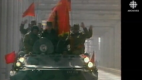 Des soldats soviétiques saluent  d'un blindé qui traverse le pont de l'Amitié entre l'Afghanistan et l'Union soviétique.