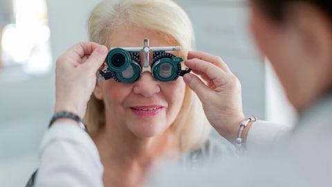 Une optométriste règle un appareil de mesure oculaire devant les yeux d'une patiente