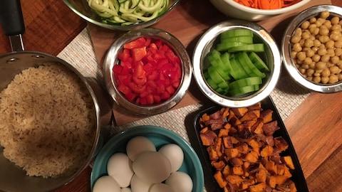 Une casserole de riz brun, de la courgette, des carottes, des poivrons, des concombres, des pois chiches, des oeufs et de la patate douce.