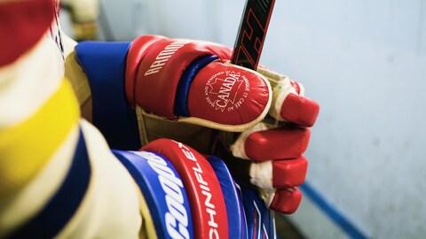 Le gant et le baton de hockey d'un membre de l'équipe de hockey les Voyageurs sur le banc
