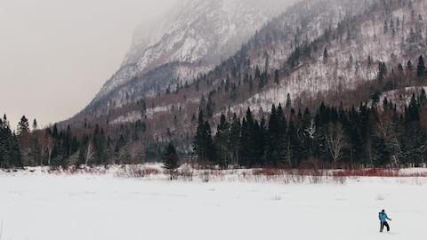 Un skieur avec un manteau bleu est au pied d'une montagne