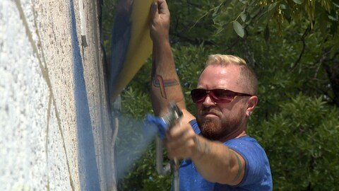 Un homme étend de la peinture sur un mur à l'aide d'un vaporisateur