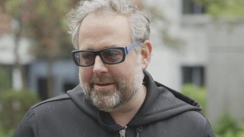 L'homme barbu porte une veste noire à capuchon et des verres teintés.