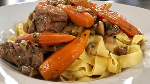 La blanquette est accompagnée de pâtes et de carottes