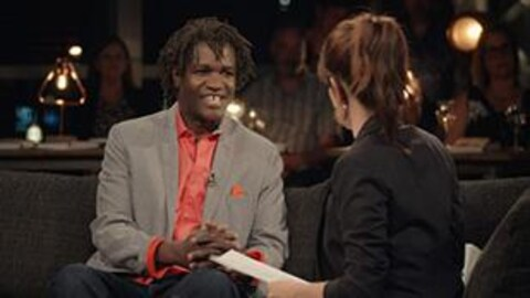 Boucar Diouf discute avec France Beaudoin sur un canapé.