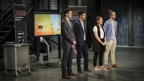 Quatre jeunes adultes sont debout devant un écran.