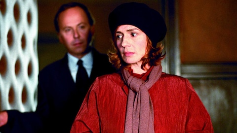 Une femme avec un chapeau noir et un manteau rouge devant un homme en complet sombre