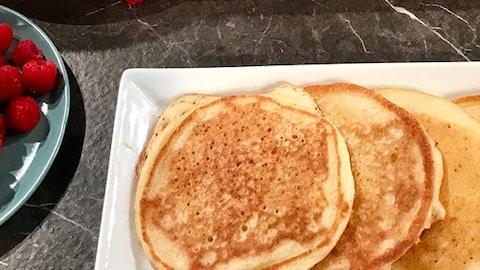 Des crêpes dans une assiette rectangulaire, une assiette de fraises et une assiette de framboises.