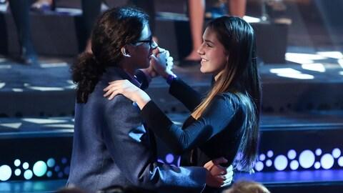 Deux jeunes chanteurs dansent en se regardant dans les yeux.