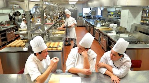 Trois chefs attablés à un comptoir en inox dans une grande cuisine industrielle.