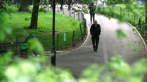 Un homme marche dans un parc.