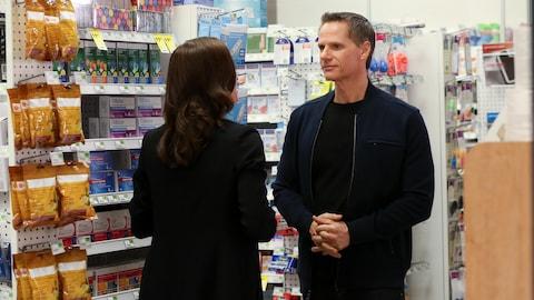 François Morency en discussion avec une femme à la pharmacie.