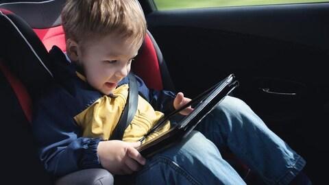 Un jeune garçon dans une voiture jouant sur un tablette