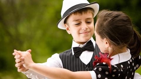 Deux enfants habillés de manière élégante font une danse en couple.