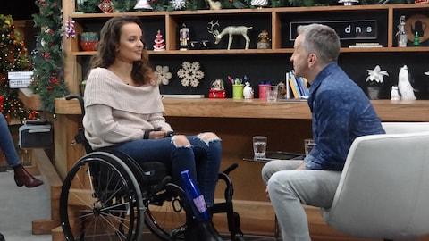 L'invitée dans son fauteuil roulant et l'animateur face à elle.