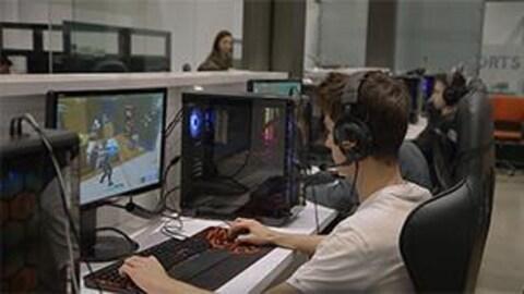 Dans une classe, des élèves jouent à un jeu vidéo sur des ordinateurs.