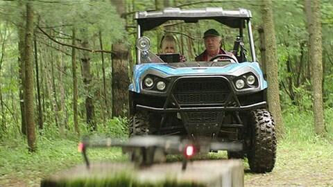 Ils roulent en forêt dans un jeep.