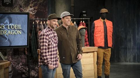 Deux jeunes hommes portent des casquettes devant un présentoir qui contient des vêtements de pêcheurs.