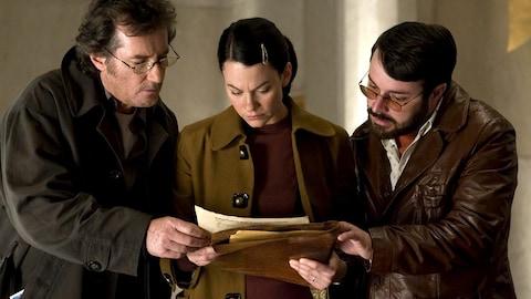 Deux hommes et une femme regardent des documents.