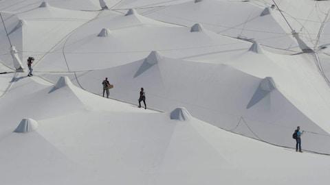 Vue de haut de quatre personnes qui marchent sur la toile du Stade olympique à Montréal.