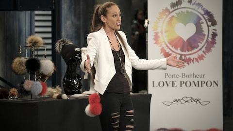 Janie porte une camisole noire, un jeans noir et un veston blanc.