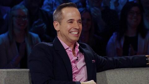 Il sourit. Il porte une chemise rose et un veston marine.