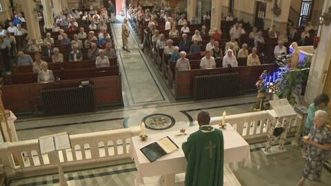Un curé préside la messe devant une foule assise dans les bancs de l'église.