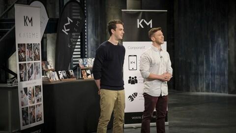 Deux jeunes hommes sont devant un présentoir d'étuis de téléphones cellulaires.