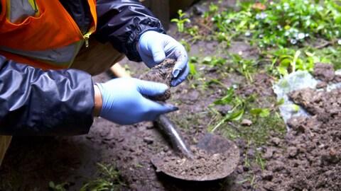 Un homme accroupi examine dans ses mains un amas de roche et de terre qu'il vient de creuser.
