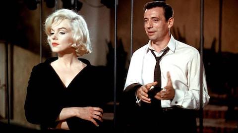 Une femme blonde en robe noire, les bras croisés, devant un homme en chemise blanche et cravate dénouée.