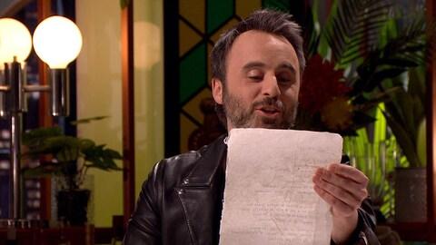 Il lit un poème sur un parchemin.
