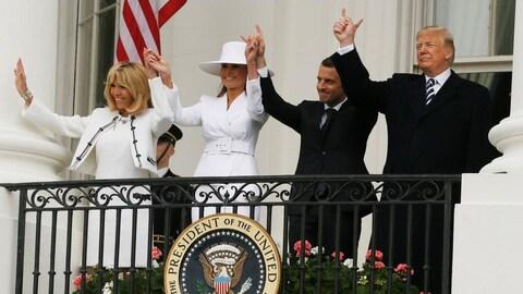 Les deux présidents et leurs épouses se tiennent par la main en levant les bras, sur le balcon de la Maison Blanche.