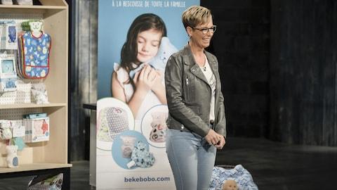Maggy-Nadyne porte un jeans bleu pâle, un t-shirt et une veste de cuir gris pâle.