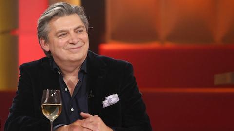 Michel Jean est à la table des invités. Il porte un veston noir.