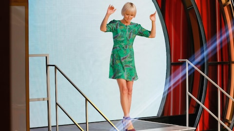 Pénélope porte une robe verte à motifs et des chaussures à talons hauts de couleur marron.