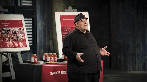 Il est devant un présentoir présentant ses sauces tomates dans des bocaux et il porte un chapeau.