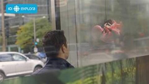 L'animateur de l'émission  Planète techno  regarde la technologie diffusée dans l'abribus du centre-ville.