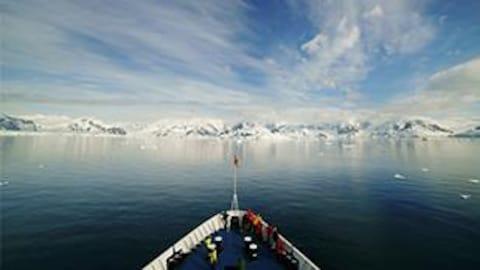 Un bateau navigue sur l'eau devant des glaciers.