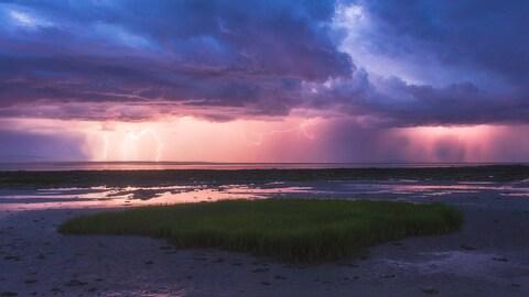 Éclairs dans un coucher de soleil sur le bord de l'eau