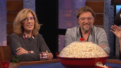 Ils sont assis autour d'une table devant un bol de popcorn géant et portent des lunettes de protection.