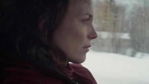 Une femme, de profil, dans une voiture.