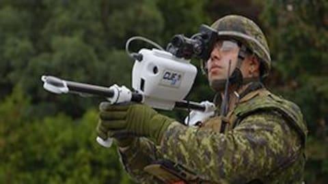 Un militaire canadien tient un appareil technologique qui ressemble à un fusil.