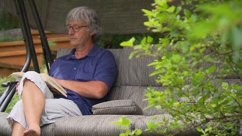 Un homme paisible lit un livre à l'extérieur.