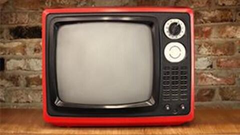 Une télévision vintage rouge est déposée devant une mur de briques.