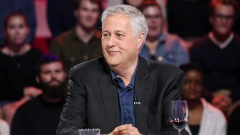 Paul Arcand, vêtu d'un veston noir et d'une chemise bleue, est assis sur le plateau de l'émission « Tout le monde en parle ».