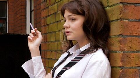 Une jeune fille en uniforme fume une cigarette adossée à un mur de pierres.